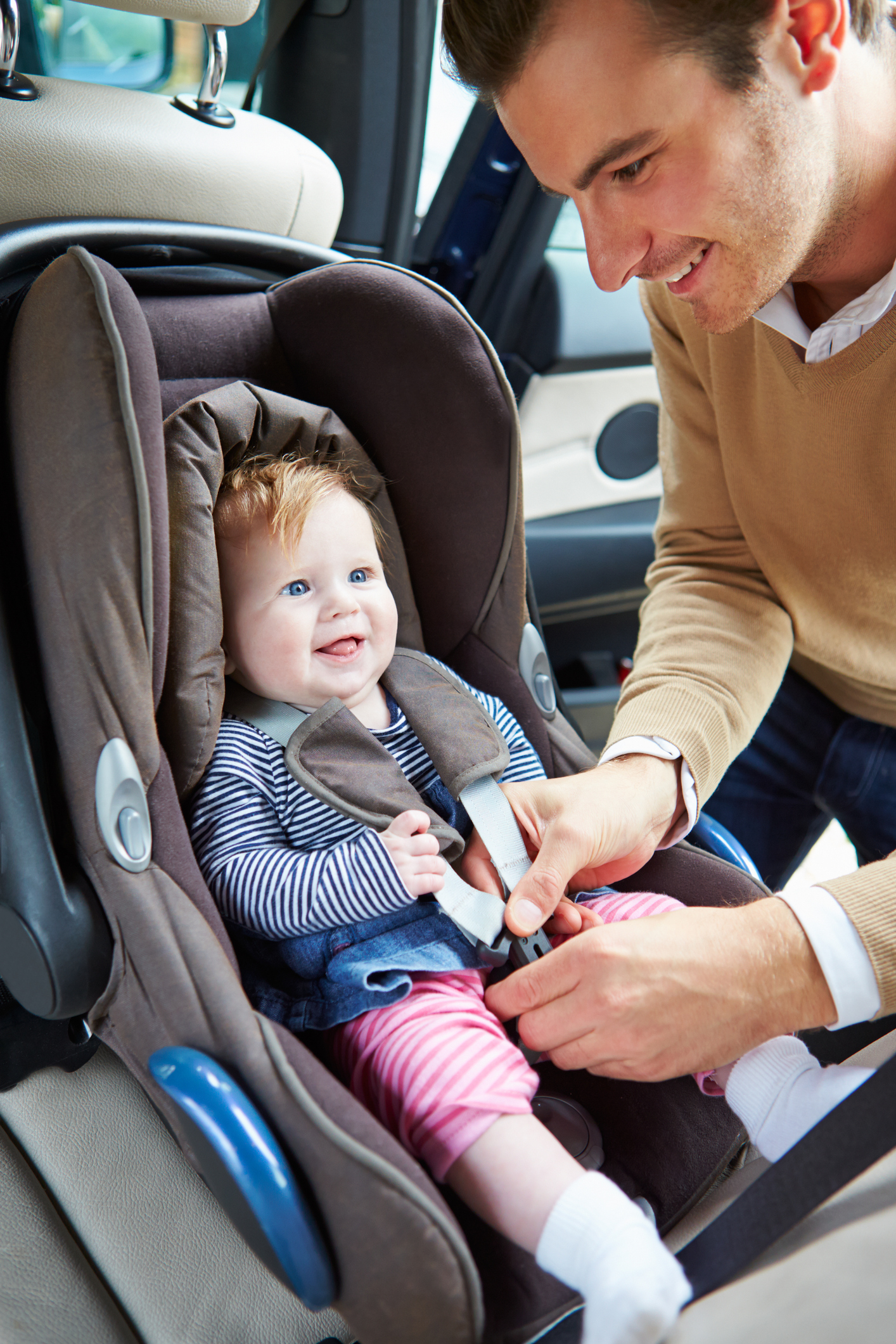 dad putting child in car seat