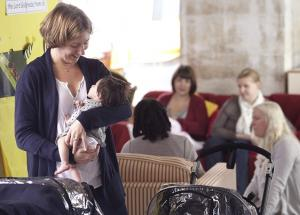 woman holding baby with group of mums sitting behind