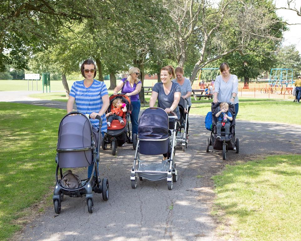 Parent with prams walking together.