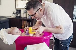 Dad bathing baby
