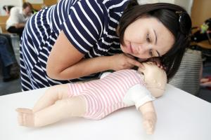 woman giving baby first aid
