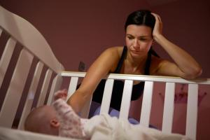 mum patting baby in cot