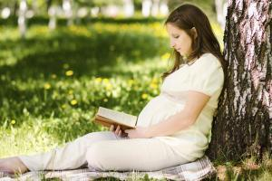 Pregnant woman reading outside