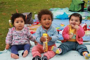 Three older babies sitting on a picnic blanket looking cute and cheeky in Newham