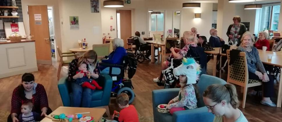 This picture shows babies, toddlers, parents, carers and older people in a care home sitting and playing together at Leeds NCT's intergenerational playgroup, held in a care home