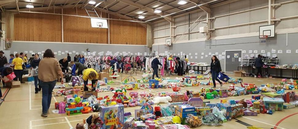 Wakefield NCT Nearly New Sale - a large sports hall with toys in the foreground and rails of clothes to the rear