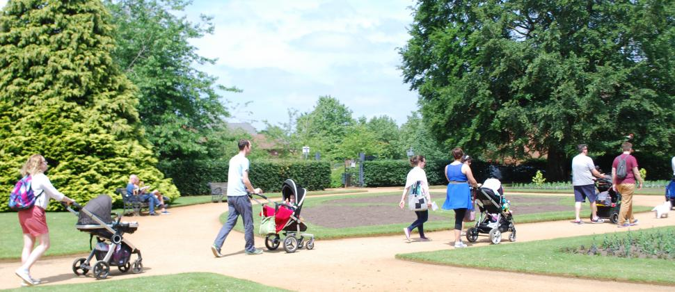 parents walking, pushing buggies on a walk and talk event