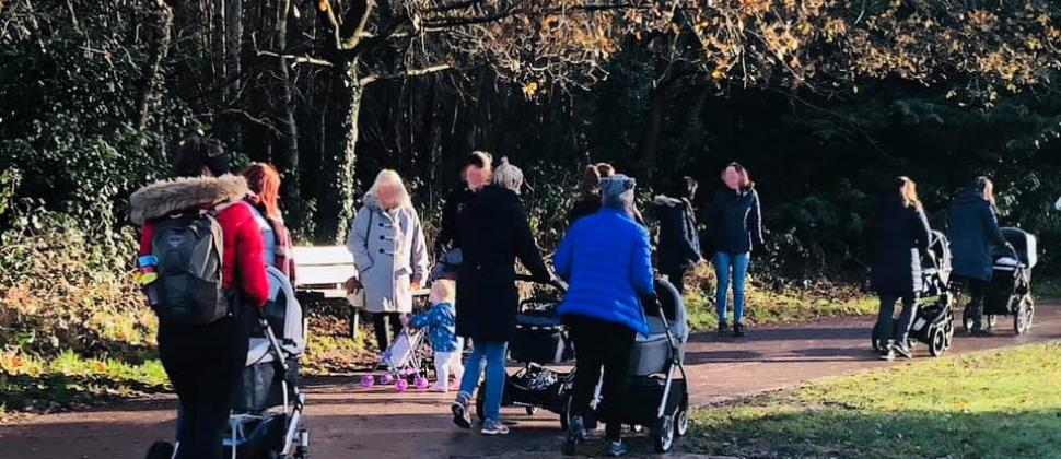 Mothers pushing their children in pushchairs on a walk